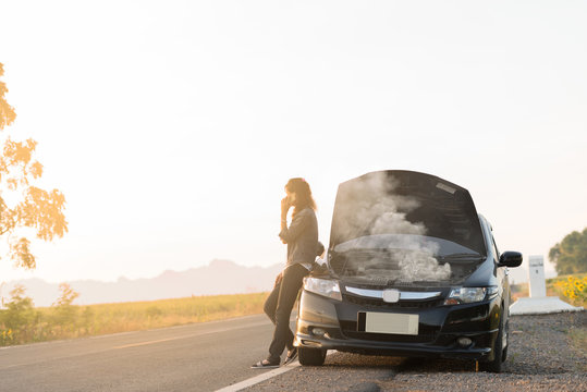 Broken car. Lady standing on the road by the broken car in the middle of nowhere. Making telephone call to get help with the broken car. smoke coming out the engine. Help needed. Car service.