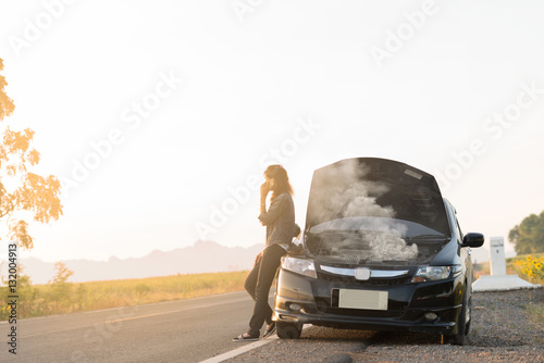 broken car lady standing on the road by the broken car in the