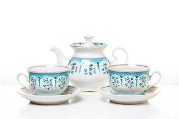 Vintage porcelain ornamental  tea set., two cups and kettle.  Decorative background.