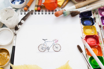 Pretty pictured bicycle with drawing supplies. Top view on artist workplace with paintbrushes, colorful dye and pencil with picture. Art, workshop, painting, inspiration, craft, creativity concept