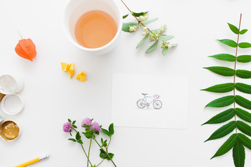 Cup of tea on artisan workplace with plants flat lay. Top view on table with picture of cute bicycle, green leaves and flowers and hot drink. Art, inspiration, craft, leisure concept
