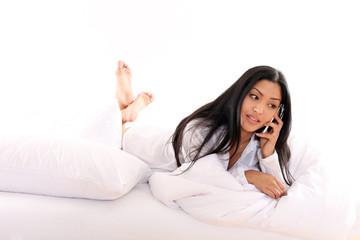 Hübsche Asiatin mit Telefon im Bett