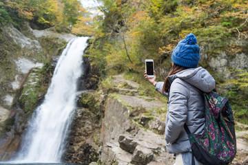 Woman taking photo on Akiu Great Falls