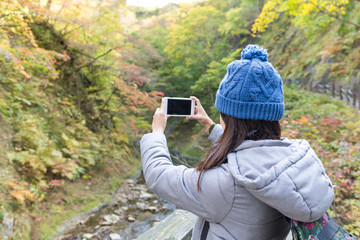 Woman taking photo in forest