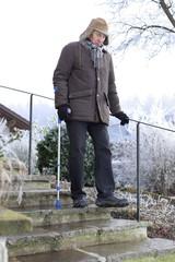 Alter Mann mit Krücken auf vereister Treppe