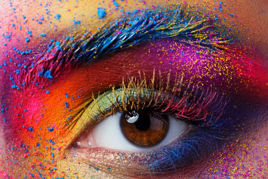 Close up view of female eye with bright multicolored fashion mak