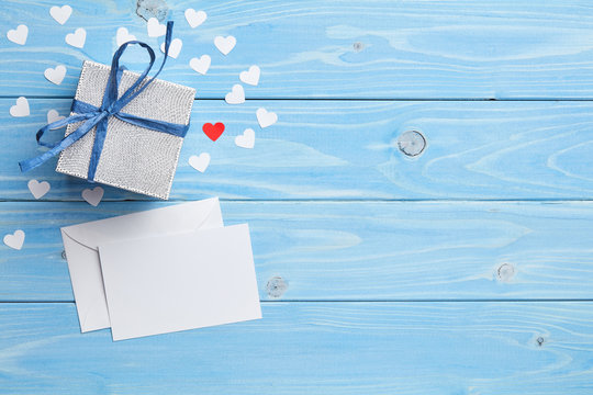 Composition of gift and white love letter on blue wooden background
