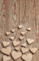 Different size heart figures on wooden background