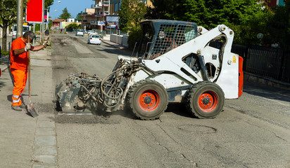 Worker checks the progress of the Milling of asphalt for road reconstruction accessory for skid steer