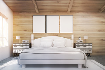 Double bed in a wooden room with posters, toned