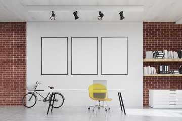 Home office with yellow chair and three posters