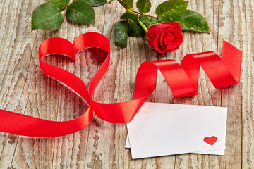 Brown wooden background with rose, letter and ribbon curled into heart