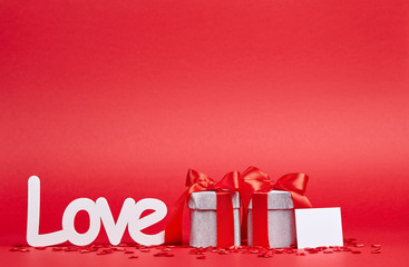 Red background with big white love sign and two gifts