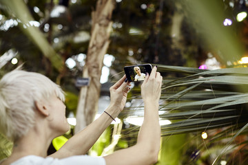 Young woman with blonde short hair is making selfie. Taking photo using phone camera in a green park. Focused on phone