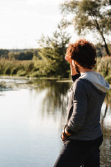 Young stylish guy enjoying calm nature landscape. Man looking at river water, back view, free space. Pacification, relax, thoughts concept