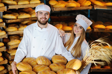 young man and woman in uniform bakers with spikelets of wheat in the hands on the background of the bakery