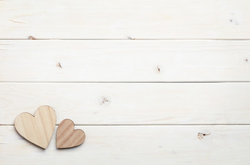 Two different size heart figures on white wooden background