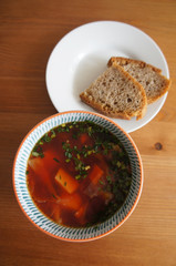 Borsch or red-beet soup with bread on wooden table