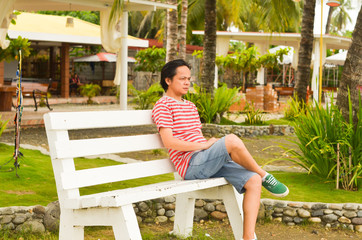 Asian man sitting on the bench thinking photo