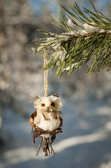 Handmade toy owl hanging on a pine branch.