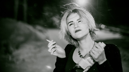 Black and white portrait of a girl with a cigarette. young beautiful woman with dyed hair smoking a cigarette in the street under the snow