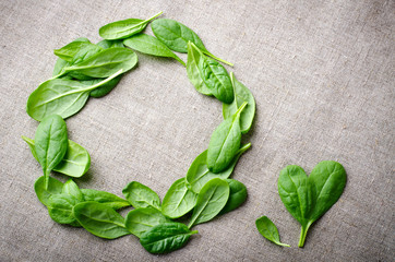 Fresh Baby spinach leaves on sackcloth background. Top view with copy space, round circle frame. Love, Healthy, Ecology concept