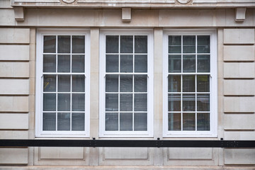 Window section with three colonial style windows in sand colored ashlar walling building facade