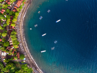 Aerial shot of calm lagoon with boats and buildings on the shore. Bali, Indonesia