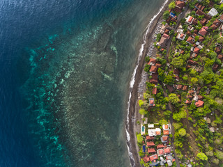 Aerial shot of underwater coral reef near shore with buildings. Bali, Indonesia