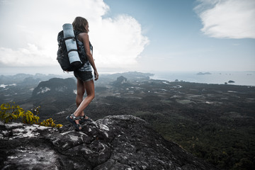 Young woman with backpack sitting on a cliff and enjoying a the view of valley