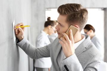 Fototapeta Praca w korporacji.  Młody mężczyzna zapisuje informację rozmawiając przez telefon obraz