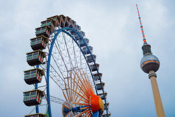 Berlin, Germany. December 13, 2016: Multicolour ferris wheel with the Television Tower (Berliner Fernsehturm) on blue sky. Photo is taken near Rotes Rathaus in Berlin