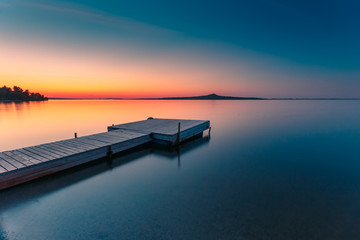 Wooden pier on a blue lake sunset and smooth reflection on water. Long exposure, Zerendi Lake, Kazakhstan.