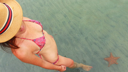 Young beautiful woman watching a starfish in the waters of Playa Estrella in Colon Island, Bocas del Toro, Panama.
