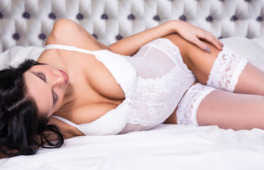 sexy young woman in white lace lingerie lying on bed