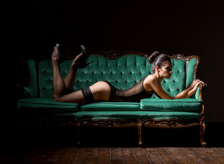 Sexy woman in lingerie on a vintage sofa