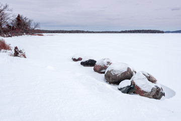 snow covered boulders on lake shoreline