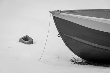 tight crop of small boat sitting in snow