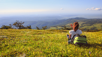 Female traveller with backpack making photo of mountain lanscape