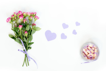 Dreams written on a pink rolled paper in a glass jar, fresh pink little roses and paper violet hearts. Flat lay on white background, top view.