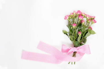 Fresh pink little roses with pink checkered ribbon. Flat lay on white background, top view.