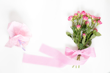 Fresh pink little roses with pink checkered ribbon and romantic gift. Flat lay on white background, top view.