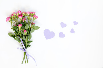 Fresh pink little roses and paper violet hearts. Flat lay on white background, top view.