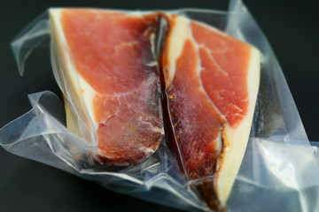 A big piece of Italian speck in vacuum packing. Tilt-shift effect applied.