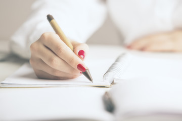 Businesswoman writing in notepad