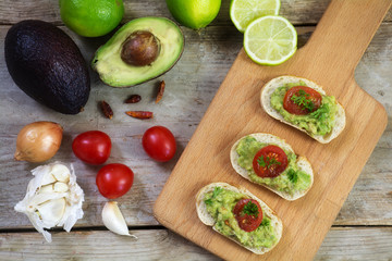 avocado cream or guacamole on baguette canapes and ingredients on rustic wood from above