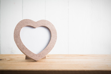 Heart shaped photo frame on wood table