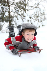 Young boy playing in the snow on an old fashioned sled