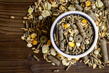 dry food for rodents in bowl wooden background top view