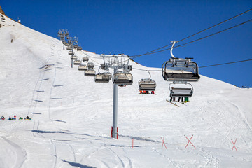 Skiers and snowboarders being transported on a chair ski lift in Sochi mountain ski resort on a sunny winter day on blue sky background